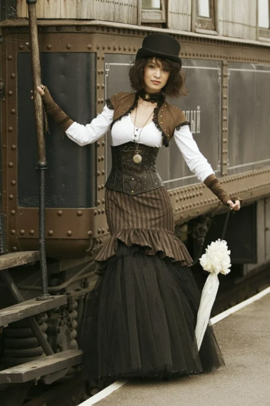 Picture of a woman wearing a Victorian corset posing in front of a train